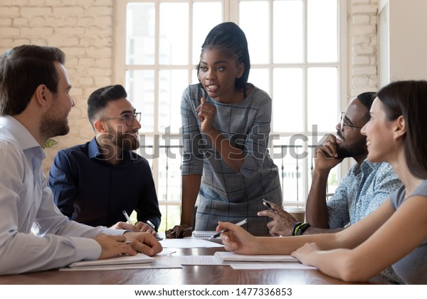 Female black executive leader talking to happy diverse employees group at corporate office briefing, multiracial coworkers listening to african woman boss explain new strategy plan at team meeting