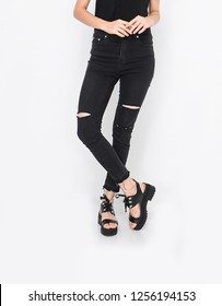 female in black jeans with black shirts and black shoes in studio