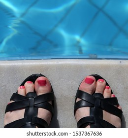 Female with black leather gladiator sandals standing by a swimming pool with turquoise water. The female has painted her toenails bright pink. Photographed during a sunny summer day on a vacation.