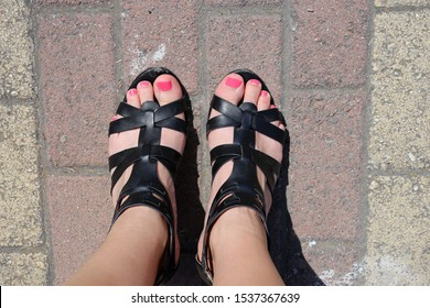 Female with black leather gladiator sandals standing on pedestrian walkway in Cyprus. The female has painted her toenails bright pink. Photographed during a sunny summer day on a vacation.