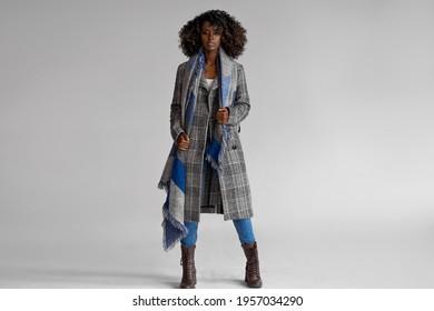 Weiblich schwarzes Modell trägt graue, geputzte Mantel mit Schal mit einer antrenigen, auf Grau isoliert angelegten, angesagten Afro-Frisur