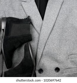Female black suede chelsee shoes on the background of a gray coat