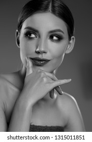 Female black and white beauty portrait. A woman holds her hand near the lips and smirks.
