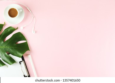 Female blog writer workspace concept. Big green monstera palm leaf on femenine desktop composition. Background, close up, copy space, flat lay, top view.
