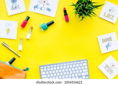 Female blogger concept. Work desk with keyboard, cosmetics and social media icons on yellow desk top view space for text