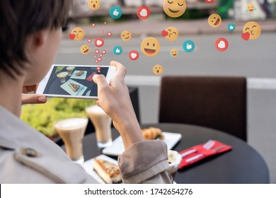 Female blogger influencer hold phone take food mobile photo on phone sit at cafe table. Girl vlogger shoot social media instagram post on smartphone get many likes emoji over shoulder closeup view.