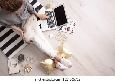 Female blogger with laptop and cat indoors, top view
