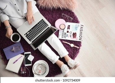 Female blogger with laptop and cup of coffee indoors, top view
