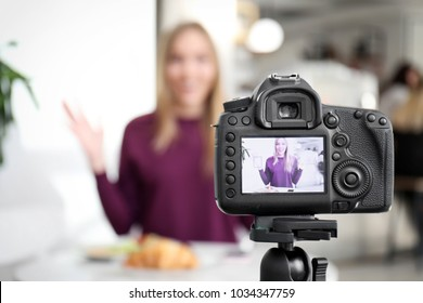Female blogger on camera screen in cafe