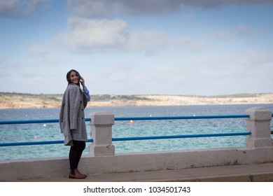 Female blogger walking  by the sea and listening to music
