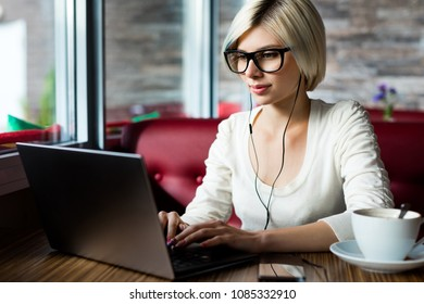 Female Blogger Wearing Glasses While Using Laptop In Cafe