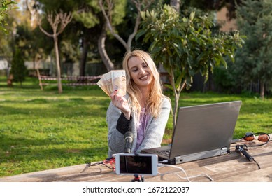 Female blond blogger demonstrates the money earned from internet services - working outdoors -  cash for review products and services - you tubers and influencers work concept