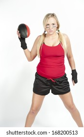A female blond model holding a red and black football wearing a red t-shirt with black shorts on a white background.