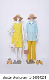 Female blue clothing with sundress and yellow trousers ,straw hat, handbag on two mannequin isolated