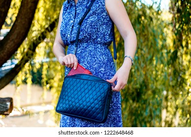 Female in a blue dress stands against the background of nature and holds a leather bag and gives a red purse. The modern concept of fashion and life style.