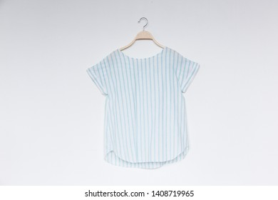 5b6de95f A female blue stripe blouse with wooden hanger isolated white background.