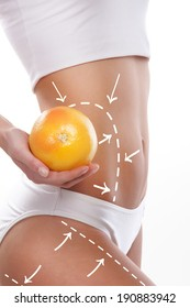 Female body with the drawing arrows on it isolated on white. Woman holding orange or grapefruit. Fat lose, liposuction and cellulite removal concept.