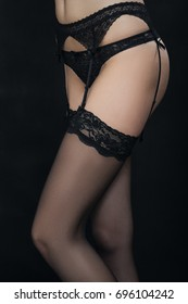 female body in lingerie and stockings on black background