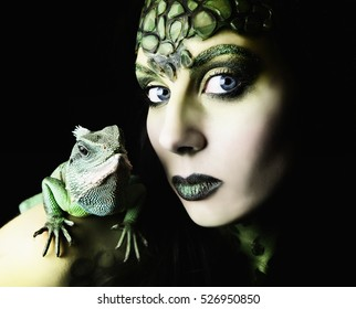 Female body painted snake goddess with lizard pet on her shoulder