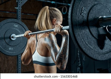Female bodybuilder doing back squats in gym Beautiful young brunette getting ready to do barbell squats wearing a black and white top Muscular young fitness woman lifting a weight crossfit in the gym