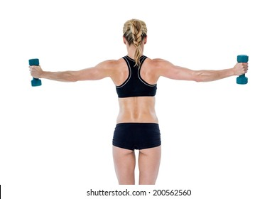 Female bodybuilder holding two dumbbells with arms out on white background