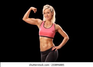 Female bodybuilder showing her bicep on black background