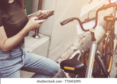 Female booking a public rental bicycle on mobile application