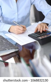 Female bookkeeper or financial inspector  making report, calculating or checking balance. Internal Revenue Service checking financial document. Audit concept in business
