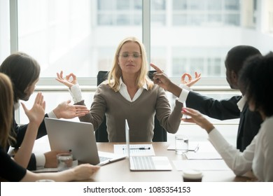 Female boss calming down meditating at stressful office meeting, peaceful mindful businesswoman practicing yoga ignoring avoiding multiracial employees at group meeting, no stress free relief concept