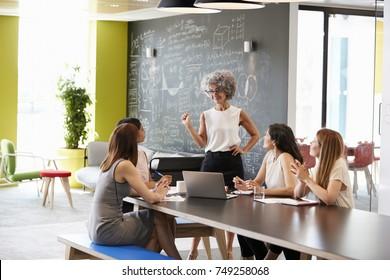 Female boss standing at an informal team meeting