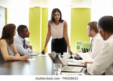Female boss stands addressing team at informal work meeting