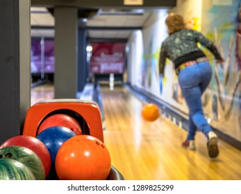 Female bowler throwing bowling ball on indoor bowling alley