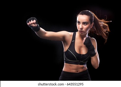 Female boxer fighting. Isolated on black background. Copy Space.