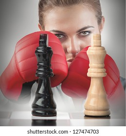 Female boxer with fists raised behind the chess board