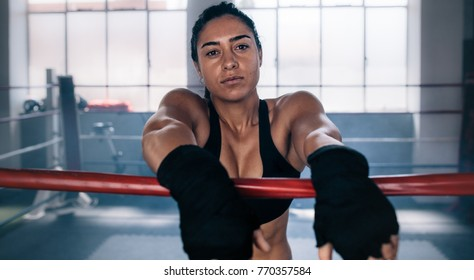 Female boxer having muscular body standing inside a boxing ring. Boxer resting her arms on the rope of boxing ring.
