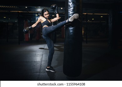 Female boxer hitting a huge punching bag at a boxing studio. Woman boxer training hard. Thai boxer punch kick by punching bag, Black bacground