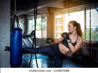Female boxer jump kicking a big blue punching bag at sport gym. Attractive woman caucasian boxer training hard doing kickboxing high kick exercise in modern fitness center.