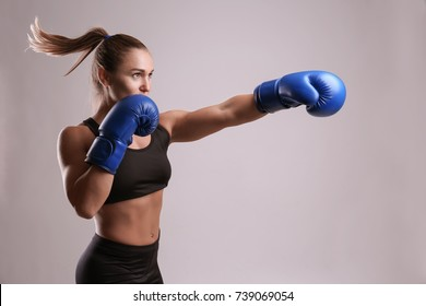 Female boxer on light background