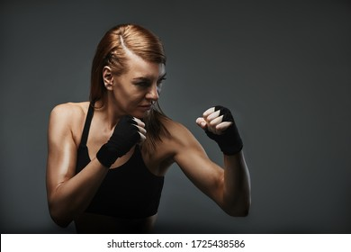 Female boxer piercing gaze, confident in boxer stance. Achieving a goal, boxing, advertising banner, copy space