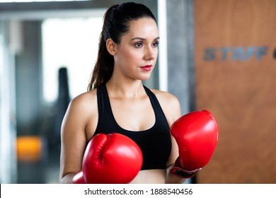 Female boxer punching bag at a boxing gym. sexy fighter girl punching actively.