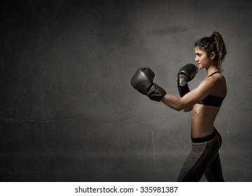 female boxer ready fot attack, dark background