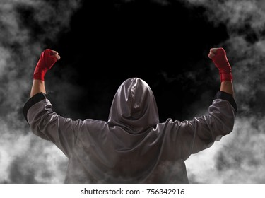 Female boxer with red boxing wraps wins the fight and bacame a champion. Victory pose. Black background with copy space.