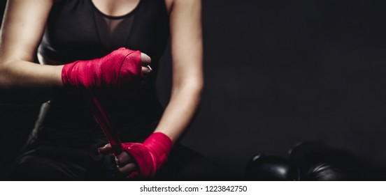 Female boxer wearing bandage gloves for ring. Concept sport. Copy space.