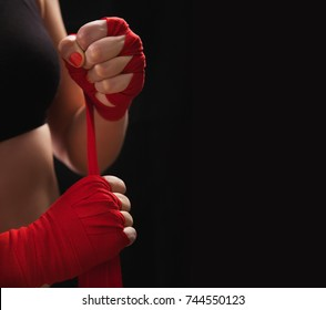 Female boxer is wrapping hands with red boxing wraps. Isolated on black background with copy space. Strong hand and ready for fight, active exercise and sparring. Close up. Women self defense.