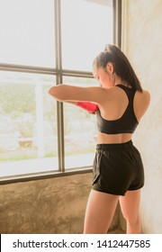 Female boxers make the fight with shadows and red boxing wraps in the gym with copy space. Strong and confident, she will be the winner.