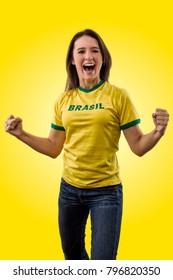 Female brazilian fan celebrating on a yellow background.