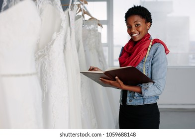 Female bridal wear designer with diary working in boutique. Female wedding dressmaker with diary in store.
