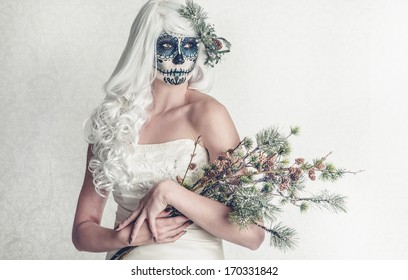a female bride with her face painted as a traditional day of the dead sugarskull mask
