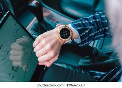 Female broker looking her smartwatch inside a car - Image