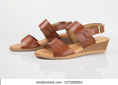 Female brown leather sandal on white background, isolated product, comfortable footwear.